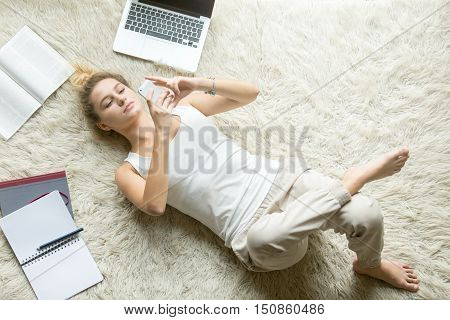 Portrait of beautiful young woman making pleasant call, texting on phone while lying on her back on white floor carpet at home, studying and relaxing at home. Top view image. Full length