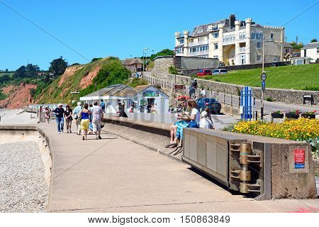 SEATON, UNITED KINGDOM - JULY 18, 2016 - Holidaymakers walking along the promenade with the beach to the left hand side Seaton Devon England UK Western Europe, July 18, 2016.