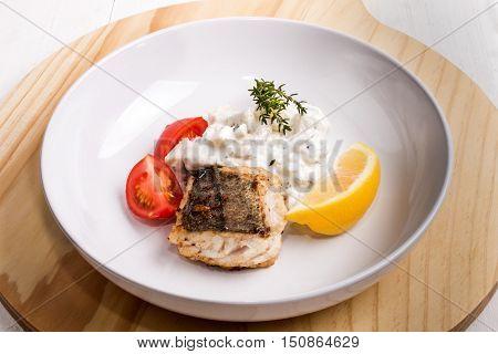 fried sea hake fillet with creamy potato puree tomato slices thyme and lemon
