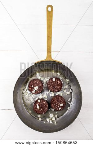 irish oatmeal black pudding with chopped onion and oil in a copper pan on an old white wooden table