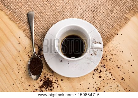 coffee cup filled with warm instant coffee a small spoon with instant coffee powder on jute