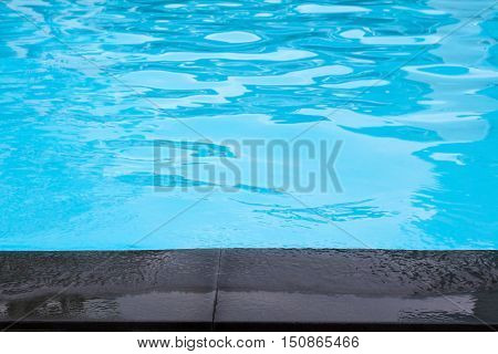 Close up edge of black cement floor near swimming pool with moving blue water
