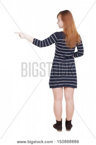Back view of  pointing woman. beautiful girl. Rear view people collection.  backside view of person.  Isolated over white background. Girl in black striped dress shows thumb to right.
