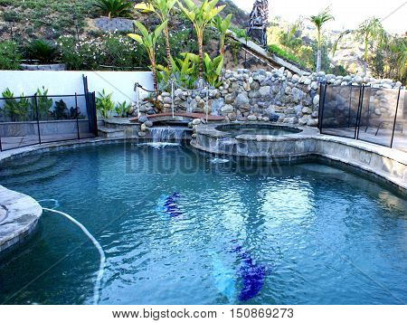 Pool and jacuzzi with a bridge and waterfall