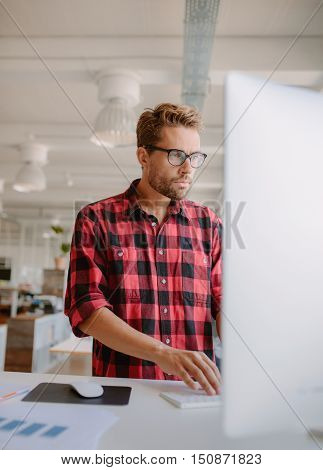 Vertical shot of young man working on computer. Businessman concentrating on his work in modern office.