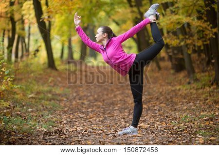 Sporty beautiful happy young woman practicing yoga, standing in Natarajasana, Dancer king pose, working out outdoor on autumn day wearing sportswear sweatshirt. Full length