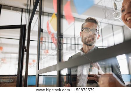 Portrait of young businessman with female colleague looking at adhesive notes on glass wall and brainstorming.