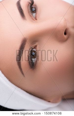 Close up of female eyes with artificial lashes. Calm young woman is lying and relaxing at beauty salon