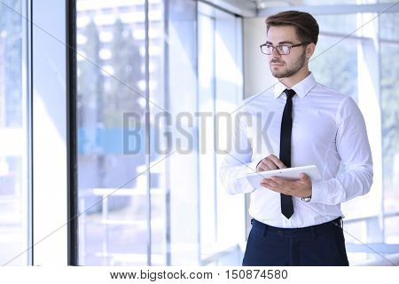 Handsome young lawyer with tablet  at office building