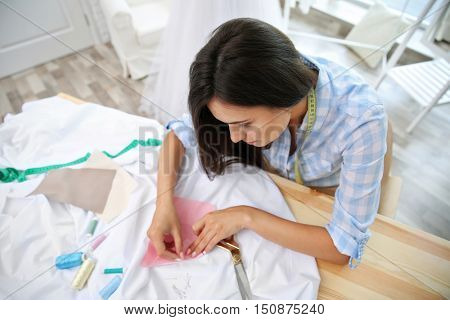 Pretty young dressmaker at workplace