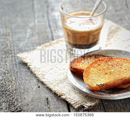 French toast on a plate and coffee with milk, napkin on a wooden background