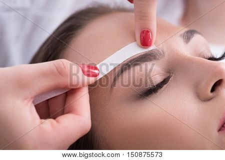 Close up of beautician hands undergoing waxing procedure for female eyebrows. She is applying in eye area