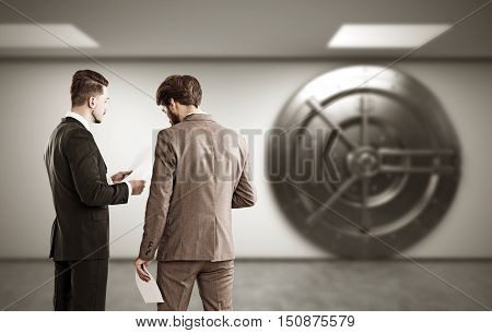 Two colleagues are discussing business issues while standing in the lobby near bank vault. Concept of collaboration. 3d rendering