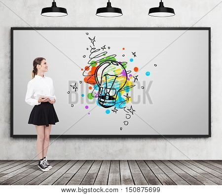 Girl in wide skirt is standing near whiteboard with colorful light bulb sketch. Concept of creativity. Mock up