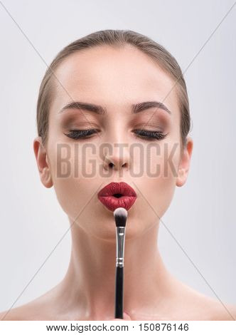 Voluptuous young girl is holding eyeshadow brush and blowing at it with sensuality. She has perfect make-up. Isolated