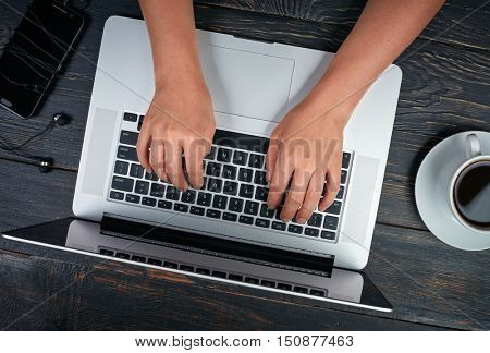 Woman's hands with laptop, smartphone and coffee. Dark vintage wooden background. Top view