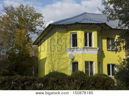 The yellow building with two floors and rectangular Windows Dating from the mid 20th century standing among autumn trees under a blue sky Russia Novomoskovsk