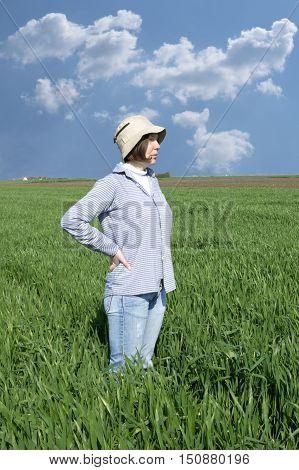 Female farmer in a weath field against blue sky.
