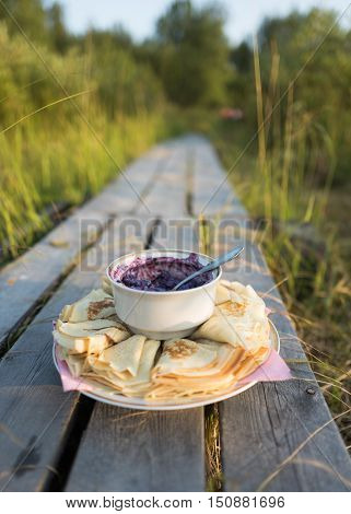 Russian pancakes with blueberry jam on the beautiful background