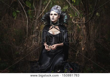 Girl strikes fear in black clothes she in the woods.