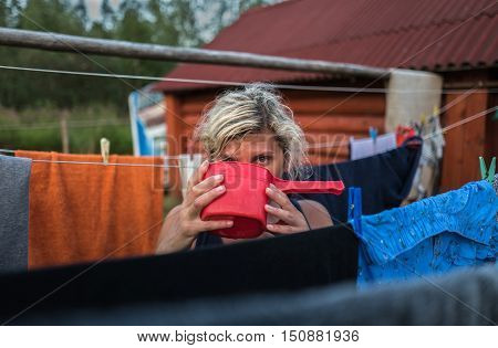 Girl is drinking water from the bucket in the village