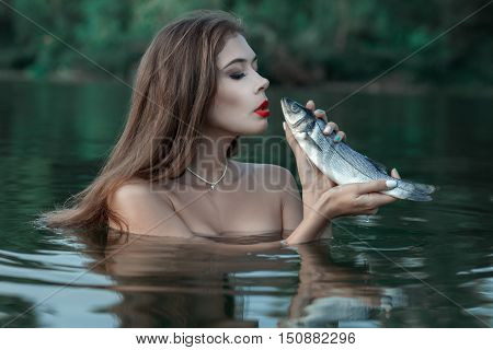 The woman is in water and talks to fish whom she has caught.