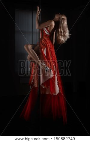 girl in red dress dancing dance Pole dance it is on the pole.