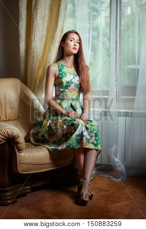In a room near a window in an armchair sits a girl in a dress.