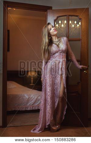 Girl in peignoir standing near the door to the bedroom.