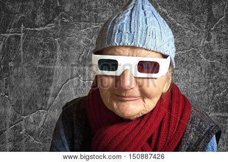 Happy elderly woman with anaglyph 3D glasses in front of the grunge concrete wall