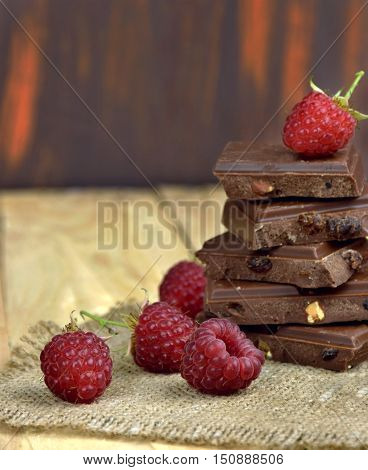 Ripe raspberries and chocolate pieces on wooden background. Close-up. Sweet Tooth. Taste of life.Cooking desserts. Holidays for the stomach.