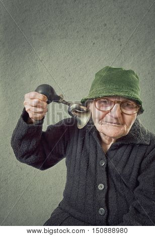 Elderly woman squeezing horn into her own ear on a vintage background.