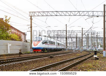 Modern hybrid electric locomotive Sapsan pulling high-speed train with railcars rzd on rails. Technical railway depot. Transport route St. Petersburg - Moscow Saint-Petersburg railway station Russia