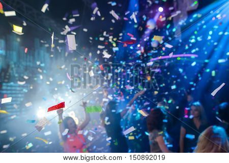 Colorful confetti falling to a crowded nightclub