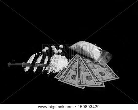 Injection syringe on cocaine drug powder lines and pile, pills, cocaine powder bag and dollar money bills on black background in black and white colors