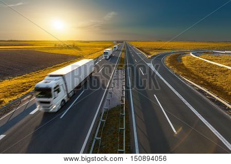 White modern delivery trucks driving towards the sun on the highway in beautiful autumn scenery. Freight scene on the motorway near Belgrade Serbia.