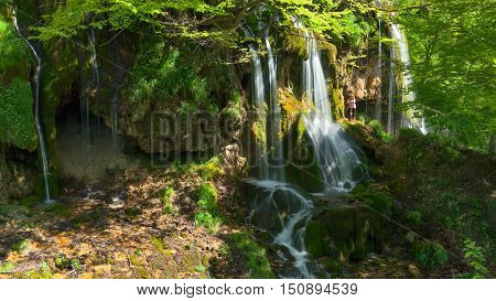 Popular travel and tourist destination in Serbia. Panorama of many Soptnica waterfalls hidden in woods at beautiful sunny day and lone woman standing next to.