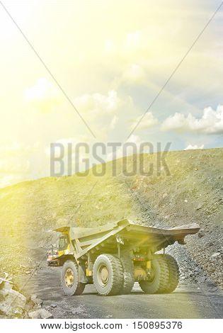 Heavy dump truck on the iron ore opencast on a summer sunset