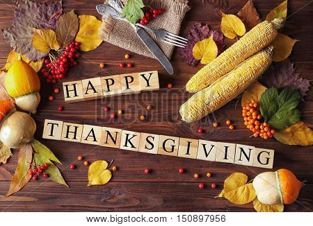 Autumn composition of vegetables, leaves, berries and wooden cubes with inscription HAPPY THANKSGIVING. Thanksgiving day concept