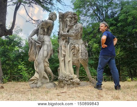 Man looking at Satyr and nymph statues mythological symbols of sexuality