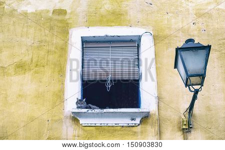 Weathered old town window with resting cat Badajoz Spain