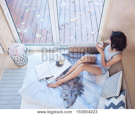 Young beautiful brunette woman with cup of coffee sitting down on the bed by the window. Top view from above. Lazy day off concept