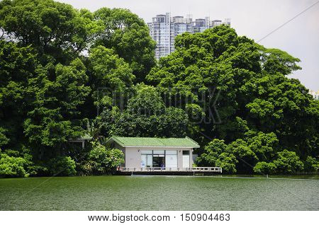 A small building on dongshan hu (east mountain lake) park surrounded by trees with a modern building in the background in Guangzhou China in Guangdong province.