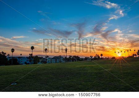 Ventura Cemetery Park showing peeking sun as it sets over ocean horizon.