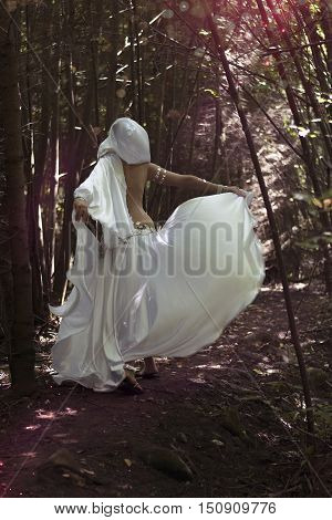 Woman in mysterious dark forest. Magical atmosphere. Fairytale