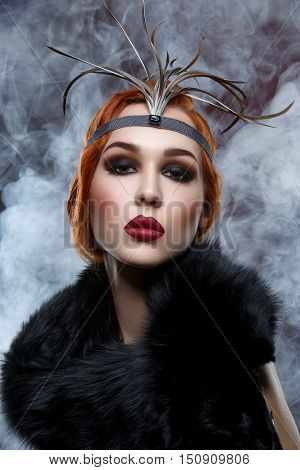 Beautiful young woman with smoky eyes and full red lips in fur. Vintage head piece. Studio beauty shot over smoky background. Copy space.