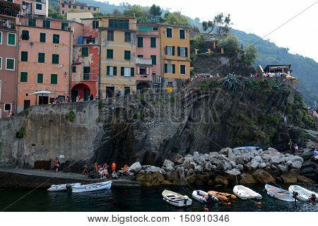 Riomaggiore Italy - September 4 2016: Buildings and boats in Riomaggiore city in Liguria Italy. One of five Cinque Terre cities (unesco world heritage). Unidentified people visible.