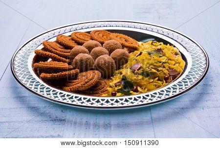 Plate full of indian festival food or diwali food or snacks like laddu, chivda, chakali or murukku, sev and shankar pale, sweet and salty snack food