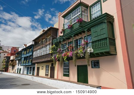 Famous ancient colorful colonies balconies decorated with flowers. Colonial houses facades in Santa Cruz La Palma island in Spain