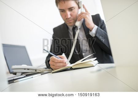 Businessman making a note in his diary as he talks on a telephone in the office scheduling an appointment.
